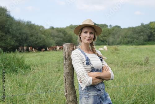 Fotografie, Tablou Smiling breeder woman standing in field, cattle in background