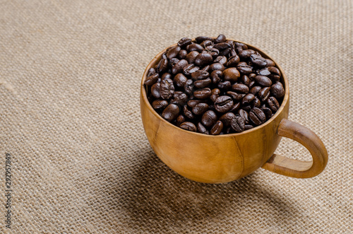 Canvas Prints Coffee beans The coffee beans in the coffee wooden cup on the hessian sack for background , texture , copy text, Love coffee concept