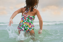 A Little Girl In A Bathing Suit Playing In The Waves At The Beach