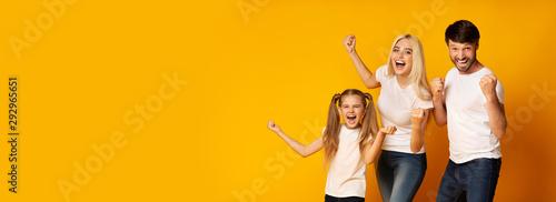Valokuva Family Of Three Shaking Fists Gesturing Yes, Yellow Background, Panorama
