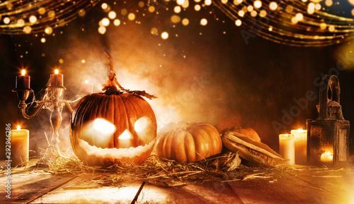 Spooky halloween pumpkin on wooden planks in dark cellar.