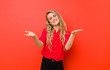Leinwanddruck Bild - young blonde woman smiling cheerfully giving a warm, friendly, loving welcome hug, feeling happy and adorable against red wall