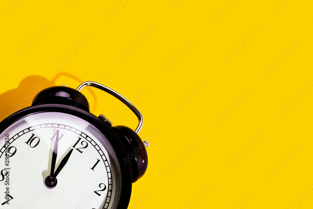 Fototapety, obrazy: Black classic style alarm clock with hard shadow isolated on yellow background with copy space. New Year and start up concept