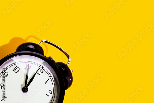 Fotografie, Obraz  Black classic style alarm clock with hard shadow isolated on yellow background with copy space