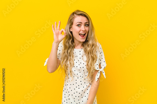 Obraz na plátně  young blonde woman feeling successful and satisfied, smiling with mouth wide ope