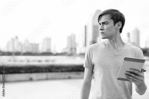 Young handsome man using digital tablet while relaxing at the park Canvas Print