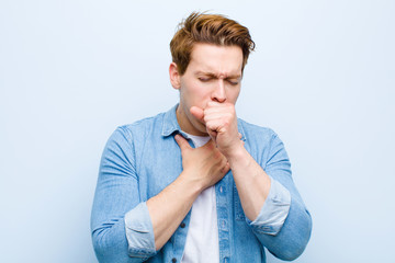 young red head man feeling ill with a sore throat and flu symptoms, coughing with mouth covered against blue wall