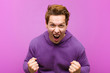canvas print picture - young red head man shouting aggressively with annoyed, frustrated, angry look and tight fists, feeling furious against purple wall