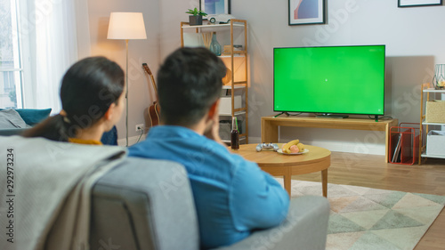 Happy Couple Sitting At Home Watching Green Chroma Key Screen Television, Relaxing on a Couch Wallpaper Mural