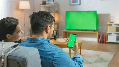 Happy Couple Sitting At Home in the Living Room Watching Green Chroma Key Screen Television, Relaxing on a Couch Canvas Print