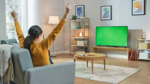 Photo  Girl Sitting At Home Sitting on a Couch, Watching Green Chroma Key Screen, Does Winning Gesture with Arms