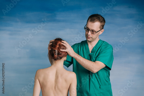 The male doctor examines the patient woman 27 years old on the blue background Canvas Print