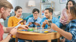 Leinwanddruck Bild - Diverse Group of Guys and Girls Playing in a Strategic Board Game with Cards and Dice. Cozy Living Room in a Daytime
