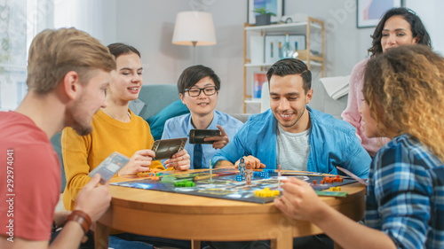 Fototapeta Diverse Group of Guys and Girls Playing in a Strategic Board Game with Cards and Dice. Cozy Living Room in a Daytime obraz na płótnie