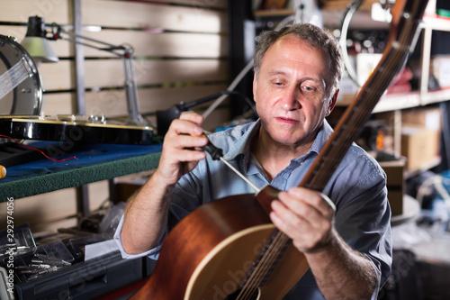 Adult man is repairing guitar in workshop - 292974056