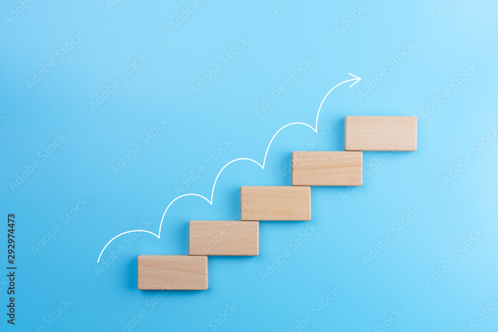 Fototapeta Wooden block stacking as step stair with white arrow up on blue background, Ladder of success in business growth concept, copy space