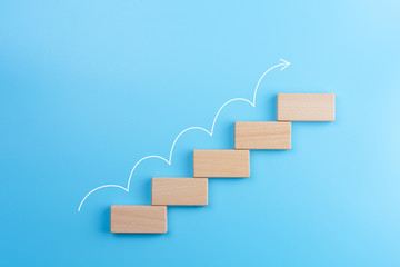 Wooden block stacking as step stair with white arrow up on blue background, Ladder of success in business growth concept, copy space