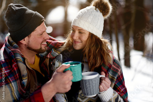 Foto auf Leinwand Schokolade Couple in love enjoying a tender moment in fresh snow during wintertime and drinking hot chocolate together