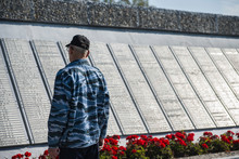 An Elderly Man Stands In Front Of A Memorial Wall With The Names Of The Victims Of The Second World War. Selective Focus.