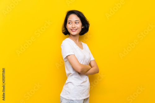 Fotomural  Asian young woman over isolated yellow wall with arms crossed and happy
