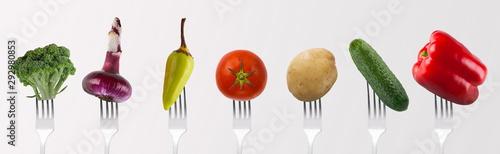 Fototapeta Collage of fresh vegetables for lunch on forks on gray obraz