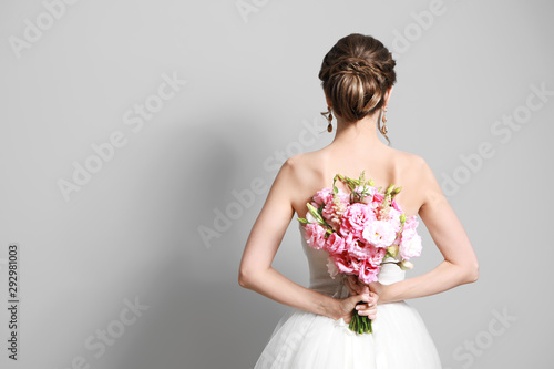 Fotografie, Obraz Beautiful young bride with wedding bouquet on grey background,  back view