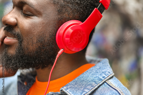 Handsome African-American man listening to music outdoors, closeup - 292981489