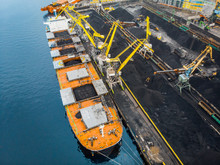 Loading Coal Anthracite Mining In Port On Cargo Tanker Ship With Crane Bucket Of Train. Aerial Top View