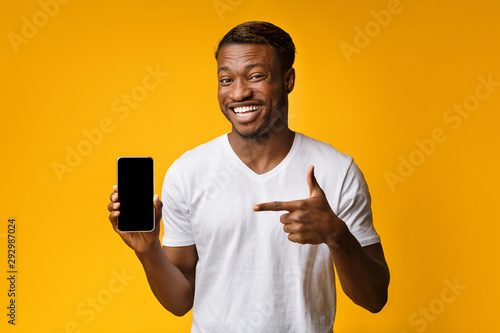 Obraz na plátně African American Man Pointing Finger At Smartphone Screen, Yellow Background