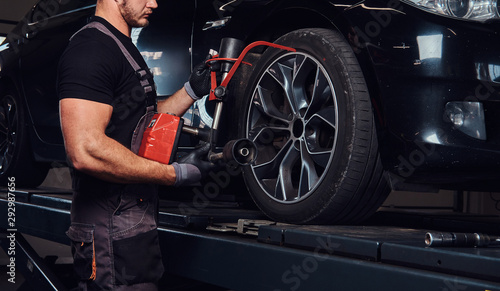 obraz lub plakat Muscular man is fixing car's wheel with special tool at auto service.
