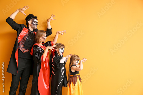 Family in Halloween costumes on color background Fototapete