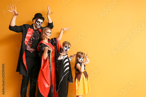 Fényképezés Family in Halloween costumes on color background