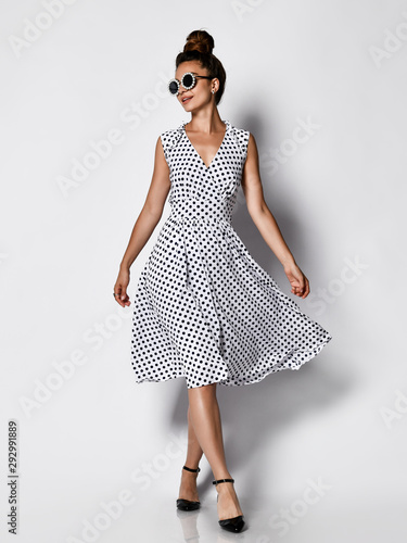 Full length portrait of happy beautiful woman in dress posing in studio isolated on white background Wall mural