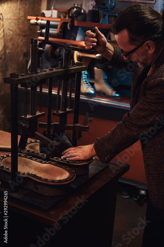 Experienced man is using a press tool at his new workshop. Canvas Print