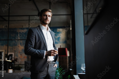 Pinturas sobre lienzo  Young handsome businessman stand and hold glass of whiskey in his own office
