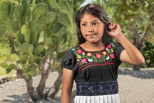 Portrait Of A Girl In Front Of A Prickly Pear Cactus. Very Cute Mexican Little Girl Portrait