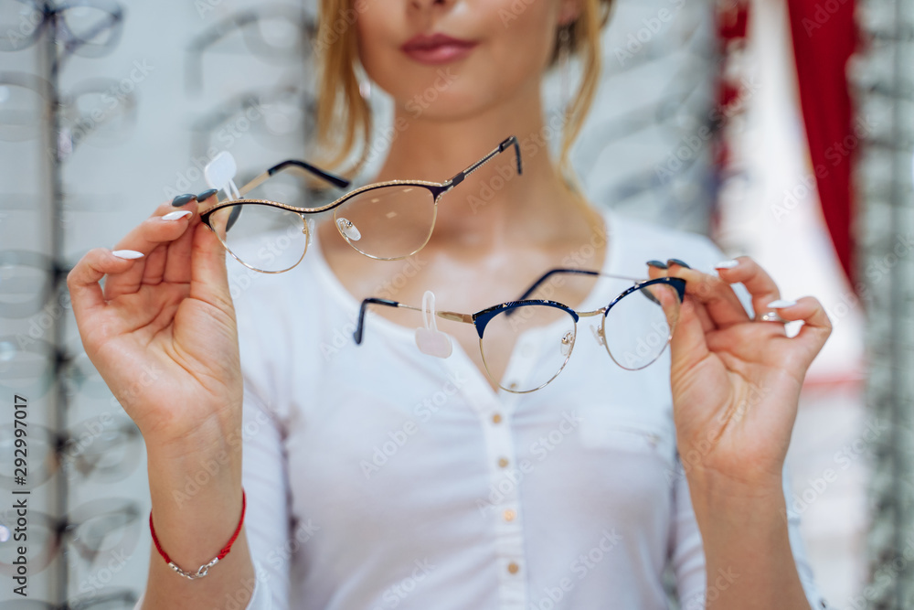 Fototapeta Pretty young woman is choosing new glasses at optical store. Eyesight correction. Ophthalmology.