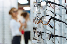 Eyeglasses Shop. Stand With Glasses In The Store Of Optics. Woman Chooses Glasses.