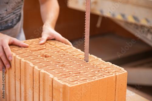 Fényképezés  Bricklayer is cutting a brick with an electrical saw