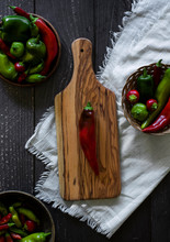 Freshly Picked Red And Green Organic Peppers, Anaheim, Shishito, Ancho Pepper, Sliced Red Pepper On Olive Wood Cutting Board With Small Knife, Pickling Summer Produce, Bowls Full Of Peppers