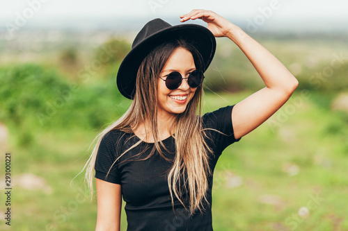 Fotomural  Portrait of young woman wearing fedora hat and sunglasses