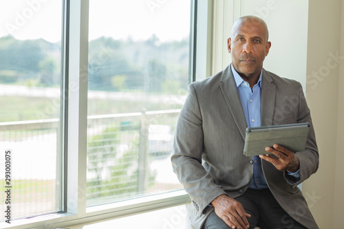 Fototapety, obrazy: Mature African American man working on a tablet.