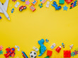 canvas print picture - Frame of kids toys on yellow background with copyspace