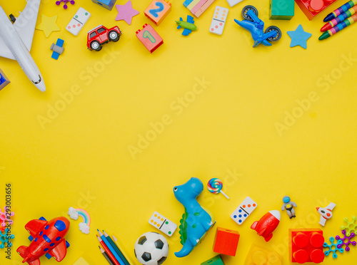 Valokuvatapetti Frame of kids toys on yellow background with copyspace