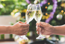 Cheerfuls Friends Toasting Sparkling Wine. Close-ups Hands Of Two Friends Toasting Wine Glass In The Dinner Party For Celebrating New Year On The Bokeh Of Light Decorate On Christmas Tree Background.