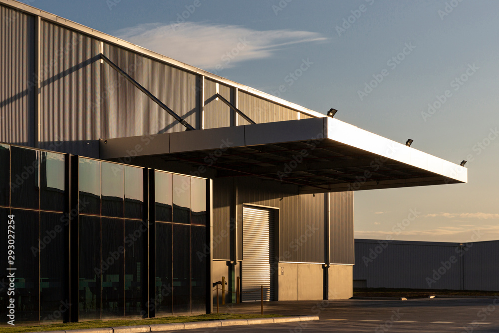 Fototapeta Industrial office & warehouse architecture bathed in afternoon light.