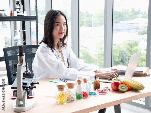 фотография  Smiling young asian female nutritionist doctor work on laptop at wooden table wi