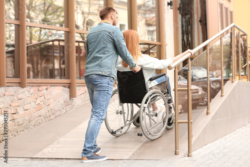Fotografie, Obraz Woman in wheelchair and man using ramp outdoors