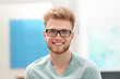 Leinwanddruck Bild - Portrait of handsome young man with glasses in room