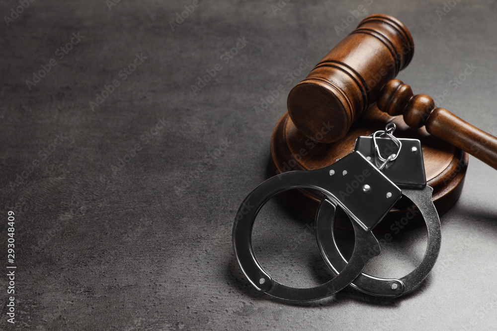 Fototapeta Judge's gavel and handcuffs on grey background, space for text. Criminal law concept